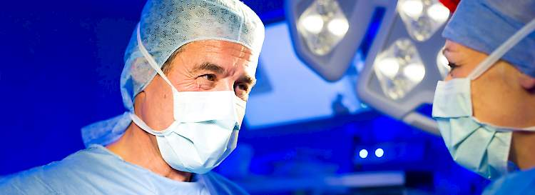 Two surgeons perform an operation and smile behind their masks.