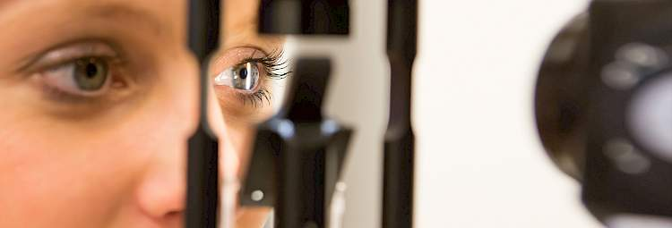 A woman receives an eye examination by an ophthalmologist